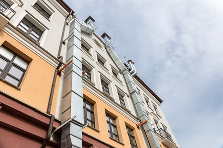 courtyard facade of urban apartment building against cloudy sky. view from bottom.