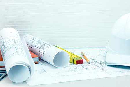contractor workplace background. architect desk with blueprints, drawing and engineering tools, safety helmet Stockfoto