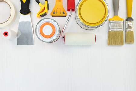 paint cans, brushes, putty knife and rollers on white wooden surface background, top view Stock Photo