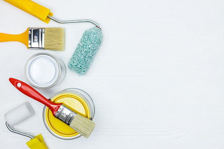 white and yellow paint cans, brushes, paint rollers on white wooden desk surface flat view