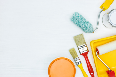 tins with white and orange paint, brushes, rollers, paint track on white wooden surface flat view Stock Photo