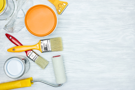 paintbrushes, rollers, knife, protective glasses and paint can on wooden grey background flat view