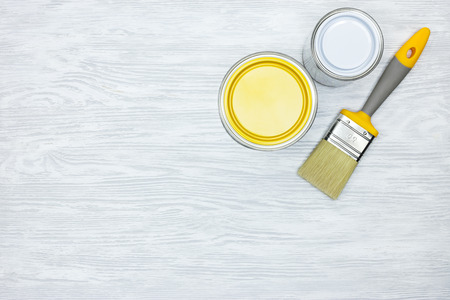 cans with white and yellow paint and paintbrush on grey wooden background Stock Photo