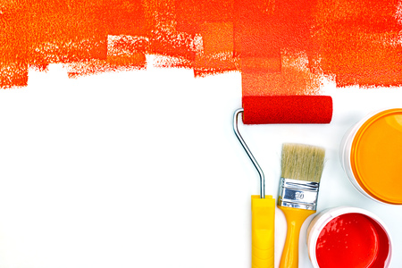 red paint strokes on white desk. red and orange paint can, brush and roller flat view
