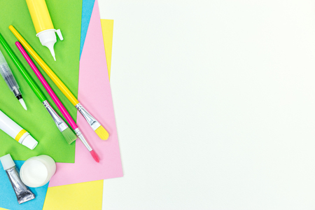 brushes, glue stick, paints, marker, colored paper sheets on white school desk background