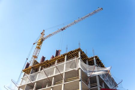 high rise construction. concrete modern building and tower crane against blue sky background