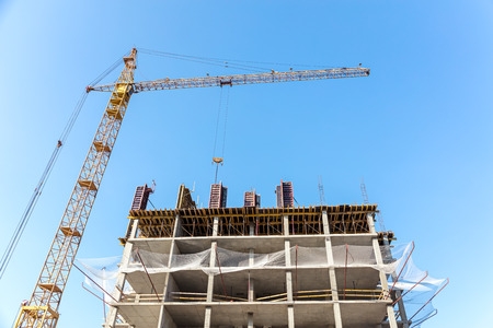apartment building under construction with yellow tower crane against blue sky
