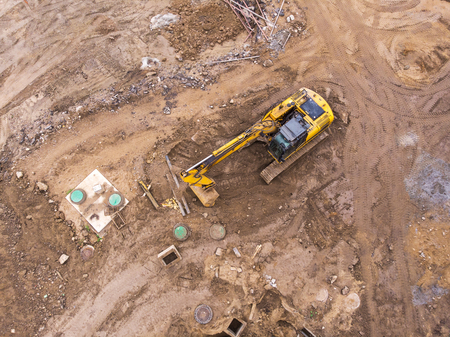 top view of construction area. yellow excavator doing earthmoving works.