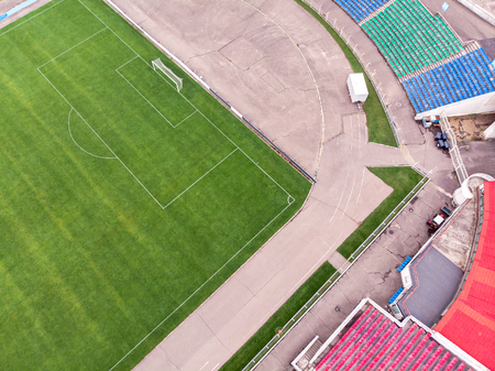 green football field and seats of soccer stadium. aerial top view