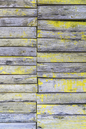 vintage grey wooden fence background with peeling yellow paint