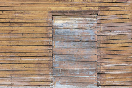 background of faded brown old wooden wall with boarded up window