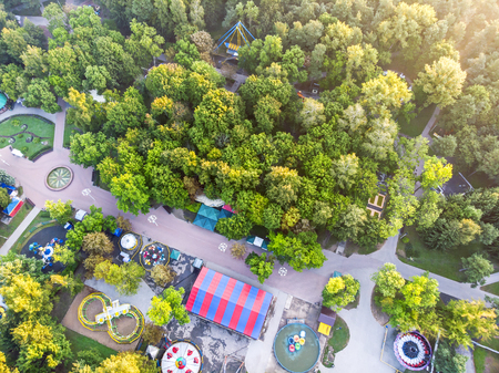 birds eye view of city amusement park among trees in summer early morning