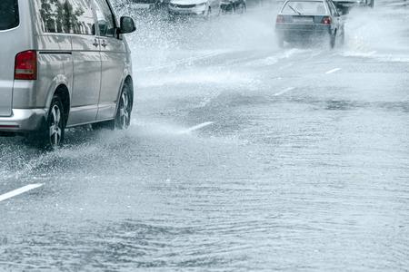 überflutete Stadtstraße nach starkem Regen. Autos fahren mit hoher Geschwindigkeit durch große Wasserpfützen
