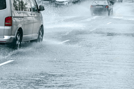 Carretera de la ciudad inundada después de fuertes lluvias. coches conduciendo a través de grandes charcos de agua a gran velocidad