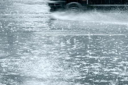 überflutete Straße bei starkem Regen. Auto in Bewegung sprüht Wasser von den Rädern