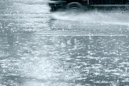 flooded street during heavy rain. car in motion spraying water from the wheels Stockfoto