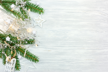 christmas tree branch decorated with garland lights and different stars. flat view