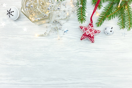 christmas ornaments with lights garland, stars and fir tree branch on wooden background Stock Photo