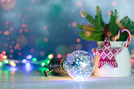 green christmas tree branches with decorative wool star, retro lamp on blue festive background with glowing lights Stock Photo