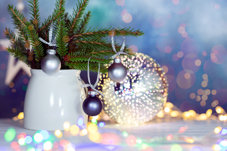 winter holiday decorations with green fir tree branches, christmas balls and glowing christmas lights Stock Photo