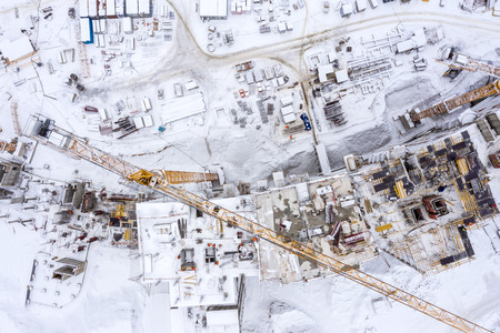 aerial top view of new city residential area under development, building machinery working under snow Stok Fotoğraf