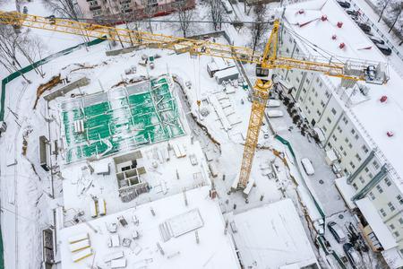 Wiederaufbau des Mehrfamilienhauses im Winter. Turmdrehkran, der auf der Baustelle arbeitet. Ansicht von oben