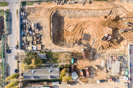 aerial photo of heavy building machinery working at city construction site