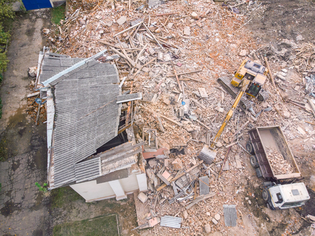 heavy construction machinery clearing out demolition site. aerial top view