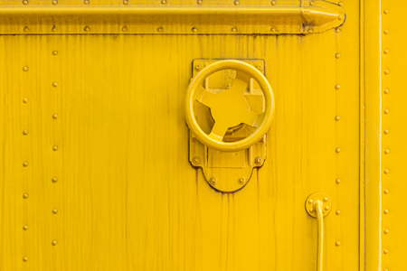 industrial valve wheel on yellow painted metal wall surface. grunge weathered background
