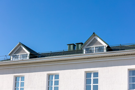 house roof with new rain gutter system against blue sky background Stock Photo