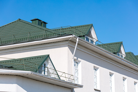 house facade. green rooftop with white metal gutter and downspout. blue sky background