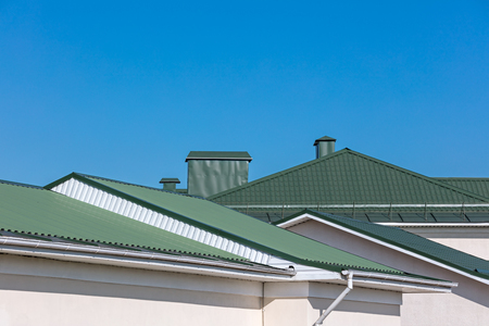green rooftops of houses with new rain gutters on clear blue sky background Stock Photo