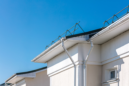 rain gutter system and roof protection from snow board. renovated roof against blue sky background