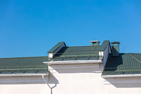 new green metal roof with drainpipe system against blue sky background