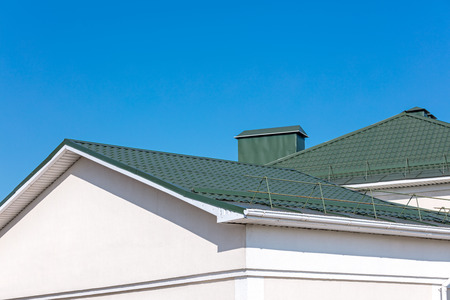 rooftop of house with new rain gutter system and roof snow guards against blue sky background