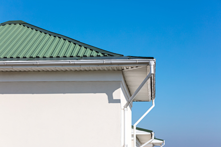 rain gutter system with downspouts on rooftop of renovated house. blue sky background
