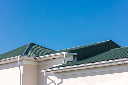 house roof with new metal drainpipe system and downspouts on blue sky background