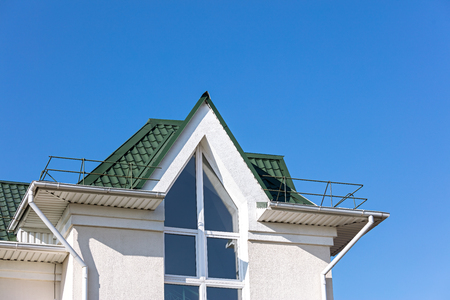 roof top of newly built house with white metal drainpipe system against blue sky background