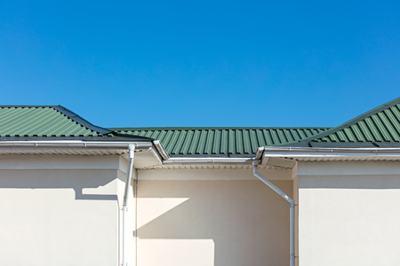 white metal rain gutter system on roof top of new house against blue sky background Stock Photo