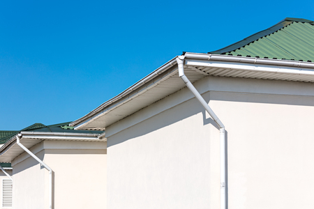 white metal drainpipes on wall corners of newly built house. rooftops against blue sky background
