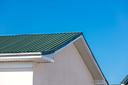 house roof, gutters and drainpipes against blue sky background