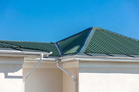 rooftop of house with metal rain gutter system and drainpipes against blue sky