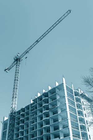 tower crane near apartment building under construction against blue sky background. bottom view