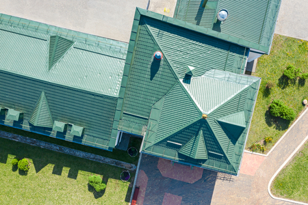 green metal shingled house roof top with installed ventilation pipes. aerial view