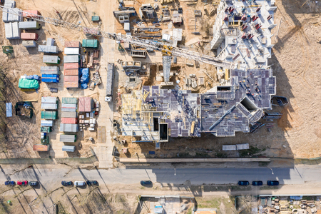 Baustelle mit Mehrfamilienhaus im Bau mit Kran und Industrieanlagen
