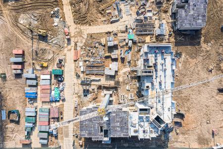 costruzione di nuovi edifici residenziali. vista aerea dall'alto del cantiere della città con gru a torre Archivio Fotografico