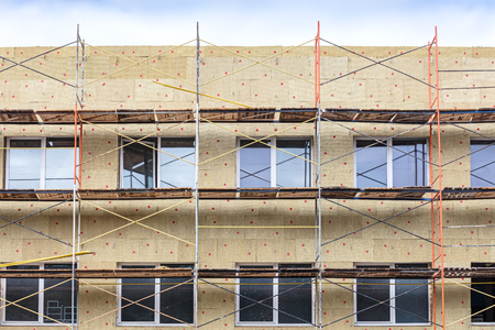 home facade insulation with rock wool. energy efficiency house wall renovation. scaffolding near the building wall