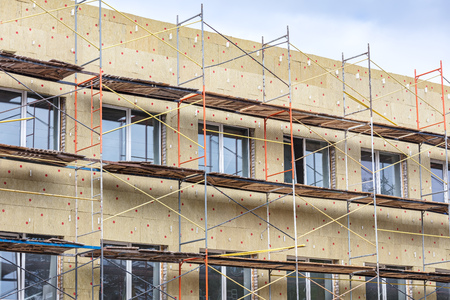 exterior wall thermal protection. building facade under renovation with scaffolding. Reklamní fotografie