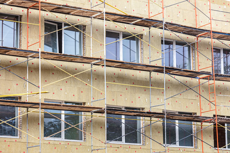 thermal insulation of house wall with mineral wool. scaffolding near facade of a building for restoration Reklamní fotografie