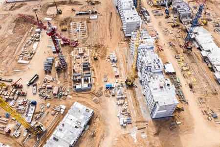 Luftaufnahme der Baustelle. Turmdrehkrane und andere Baumaschinen, die beim Bau neuer Stadtwohnungen arbeiten Standard-Bild